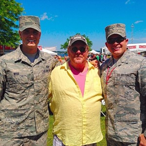 "Mario Batali poses with two members of the National Guard while taping a segment for ""The Chew"" at the National Cherry Festival in Traverse City."